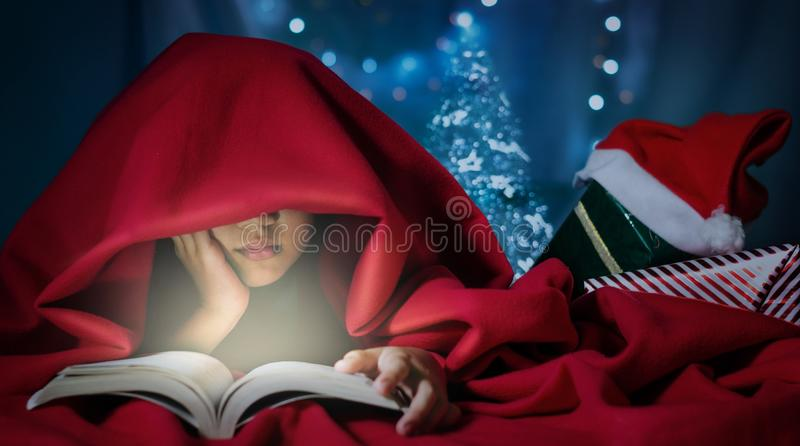 Kid reading a book on the bed. royalty free stock photos