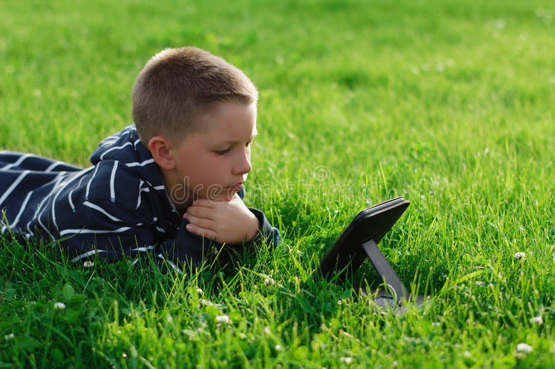 Kid reading an ebook in a park. Over green grass stock photo