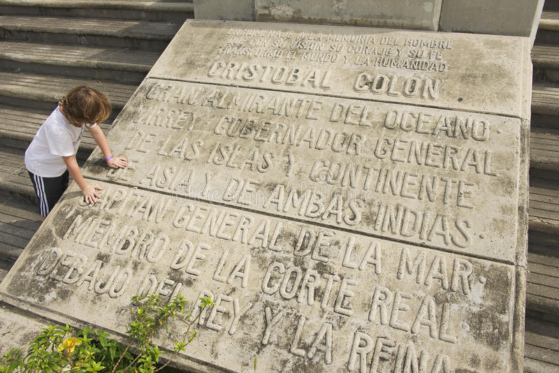 Kid reads the Memorial plaque at the entrance to the Columbus Lighthouse in Santo Domingo, Dominican Republic royalty free stock photo