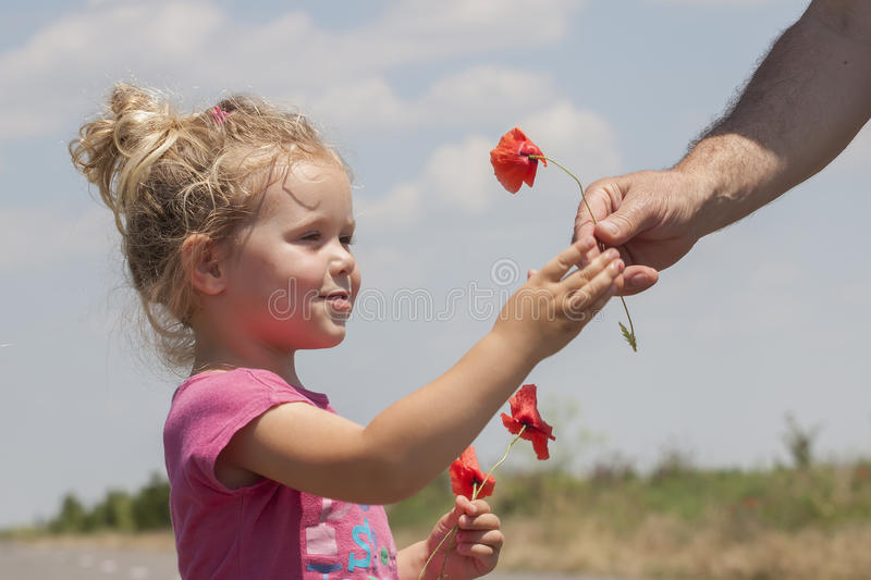 Kid receiving flowers. From a man royalty free stock images