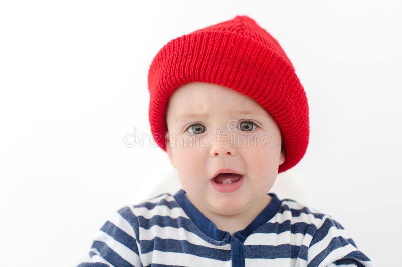 Kid in red hat is indignant two first teeth studio royalty free stock image