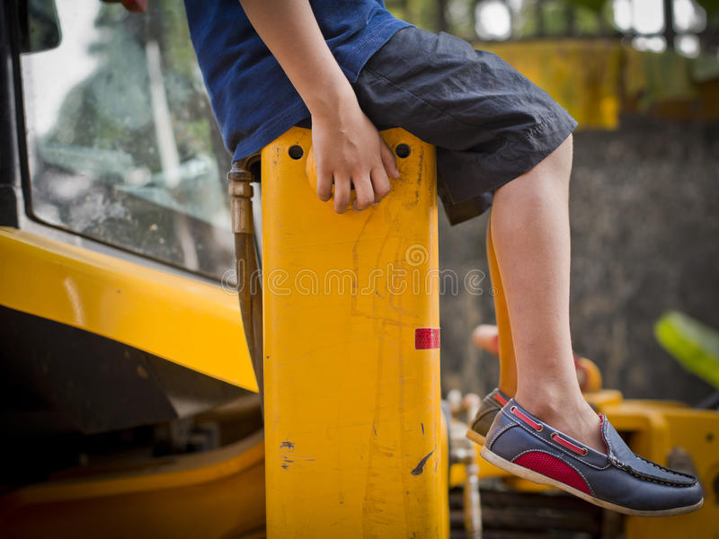 Kid Relaxing on top of an Excavator. stock images