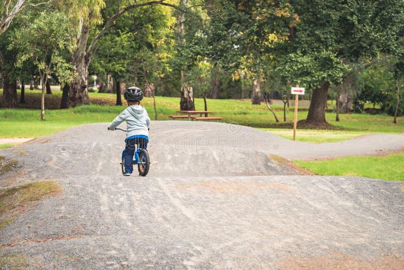 Kid riding a balance bike stock image