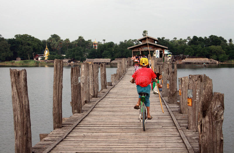Kid riding bike on U-Bein bridge in Mandalay
