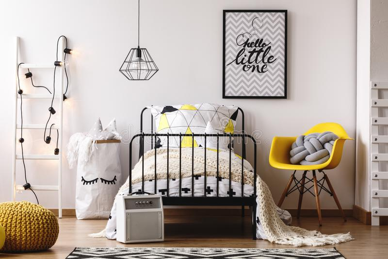 Kid`s bed with beige blanket. Grey pillow on yellow chair next to kid`s bed with beige blanket and triangle pattern pillow stock photos