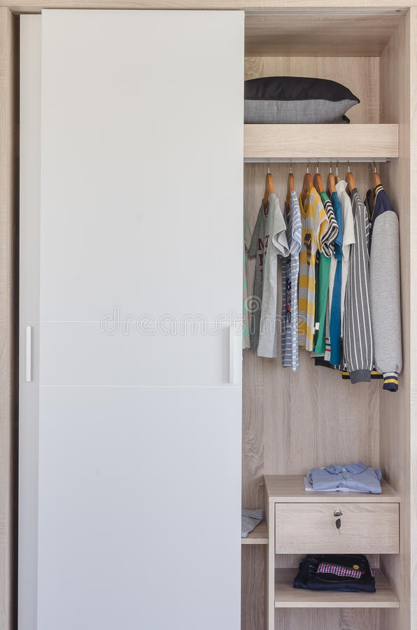 Kid's clothes hanging in white wardrobe. At home royalty free stock image