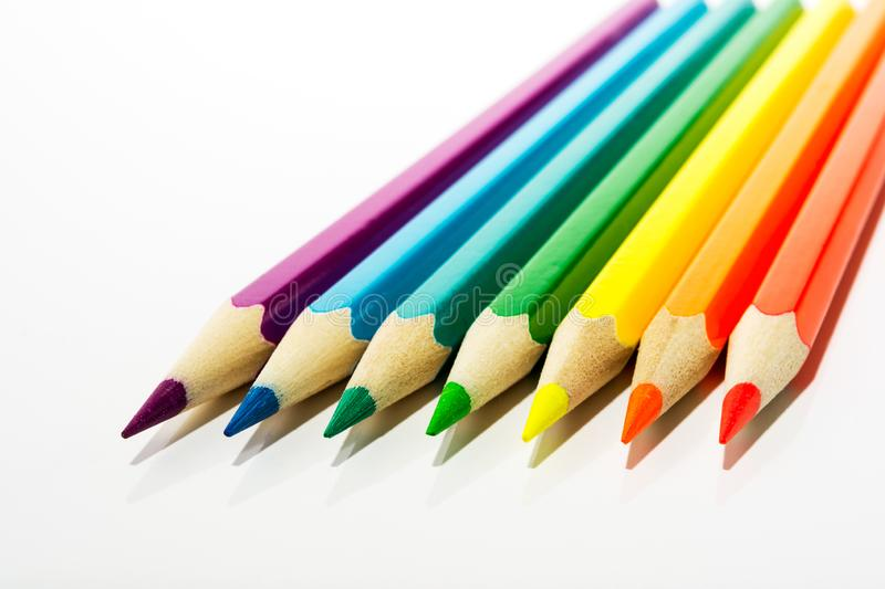 Kid`s colored pencils as a symbol of first steps of artist. Red, orange, yellow, green, blue, purple kid`s colored pencils as a symbol of first steps of artist royalty free stock photography
