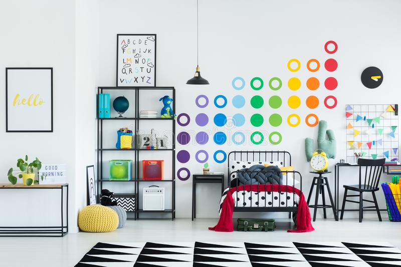 Kid`s colorful room. Kid`s spacious colorful room with knot pillow on the bed, decorations, desk and posters stock photo