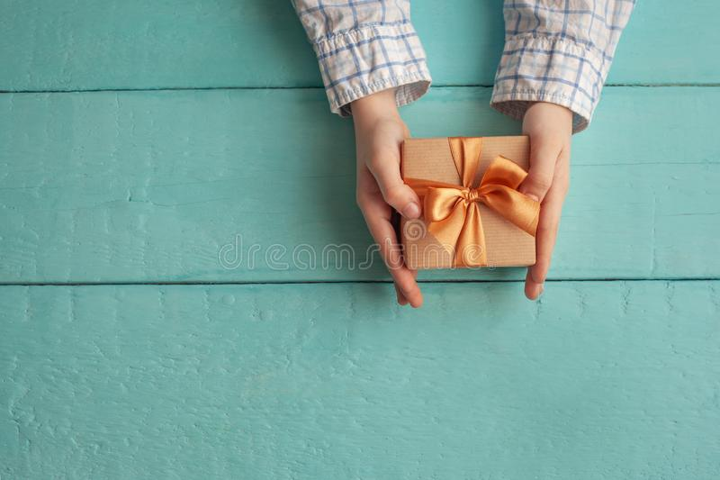 Kid`s hands holding gift box wrapped in craft paper and tied with bow. Concept Father`s Day or Birthday background royalty free stock photos