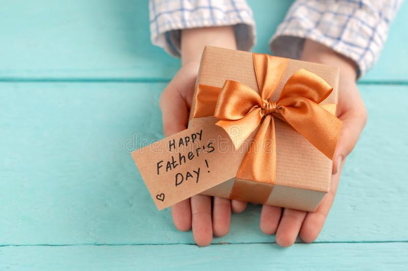 Kid`s hands holding gift box wrapped in craft paper and tied with bow. Concept Father`s Day or Birthday background royalty free stock photo