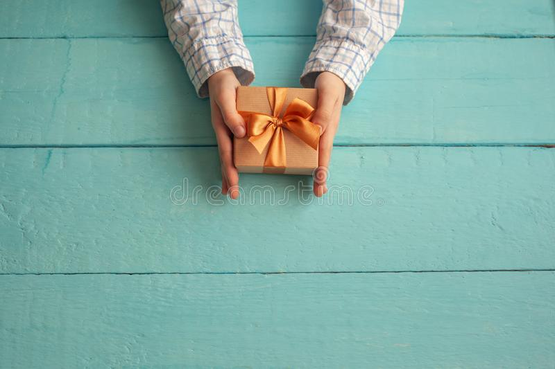 Kid`s hands holding gift box wrapped in craft paper and tied with bow. Concept Father`s Day or Birthday background stock photography