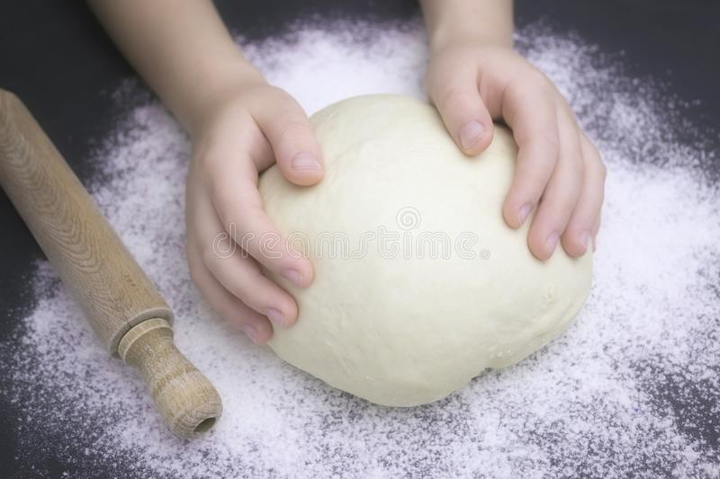 Kid`s hands, some flour, wheat dough and rolling pin on the black table. Children hands making the rye dough for backing bread. stock photography