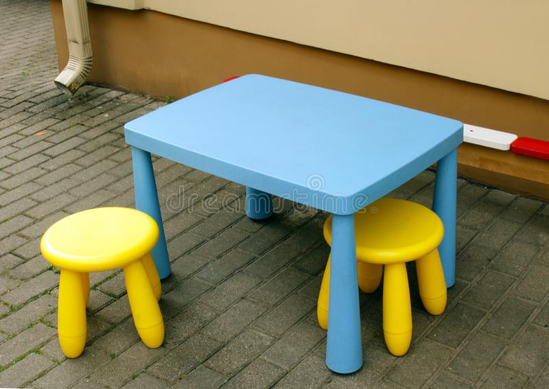 Kid& x27;s outdoor furniture blue table and yellow chairs on tiled pavement. Kid& x27;s outdoor furniture blue table and yellow chairs, apartment, armchair stock image