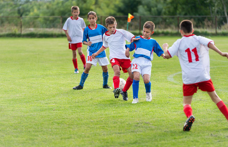 Kids soccer. Little kids playing defense in football match royalty free stock photography