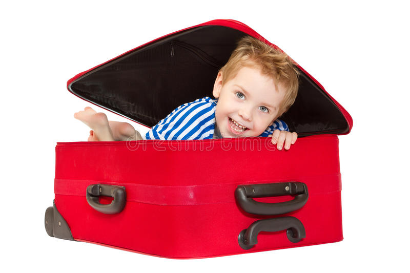 Kid in sailor suit looking out suitcase. Kid in sailor suit looking out red suitcase. Isolated on white stock photos