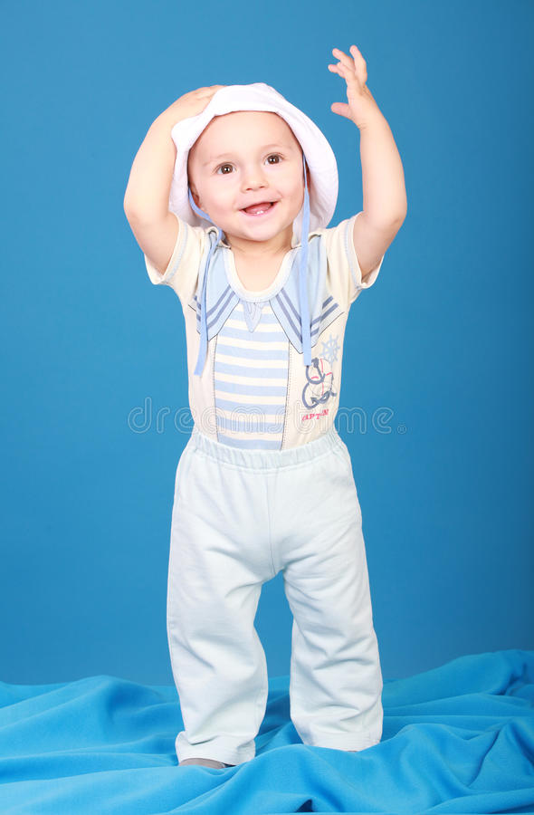 The kid in the sailor suit standing and smiling. The kid in the sailor suit standing there smiling, raising his hand to the top. Blue background royalty free stock photos