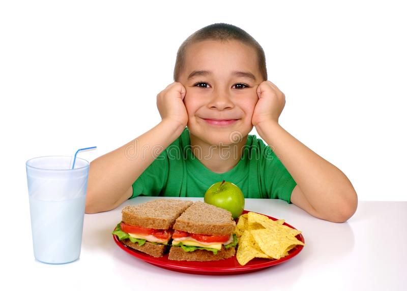 Kid with sandwich. Six year old Hispanic boy ready to eat a nutritious meal of whole wheat meat and cheese sandwich, tortilla chips, apple, and milk, shot on stock image