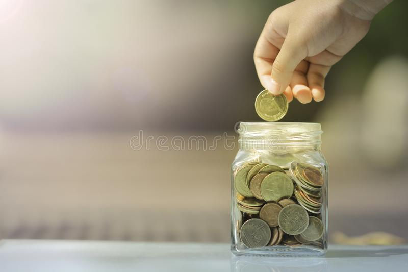 Kid saving coin in glass piggy bank royalty free stock photos