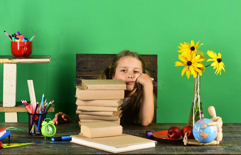 Kid and school supplies, green background. Girl with bored face stock photo