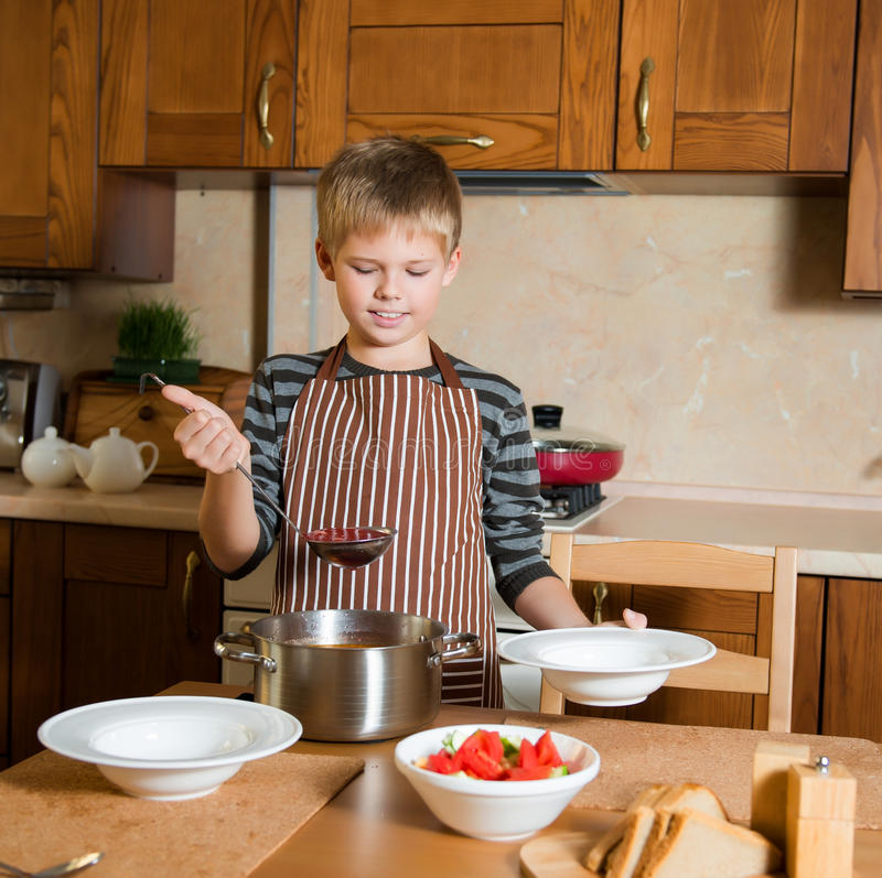 Kid serving Borshch, traditional Russian and Ukrainian soup. Pouring soup into a plate with ladle from pan in kitchen. Boy serving Borshch, traditional Russian royalty free stock photos