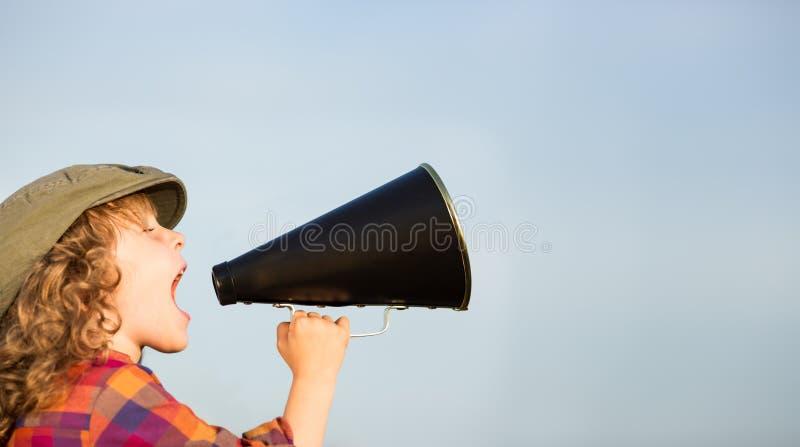 Kid shouting through megaphone stock photo