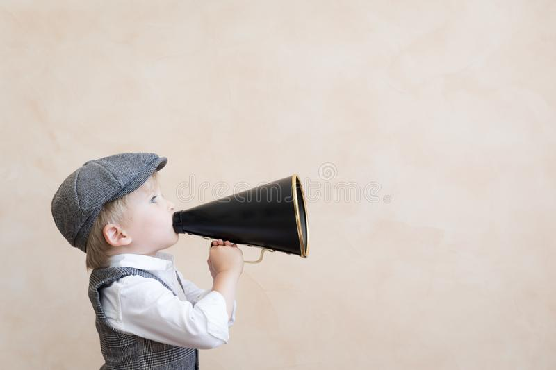 Kid shouting through vintage megaphone stock photography