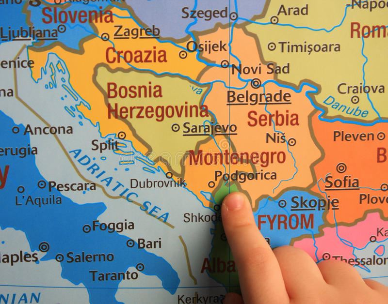Kid showing a Balkan on the map and Montenegro royalty free stock photos