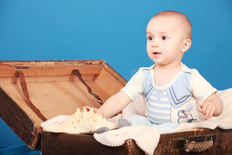 Kid sits in a chest in a sailor suit. A little boy sits on a blue background in a chest in sailor suit royalty free stock images