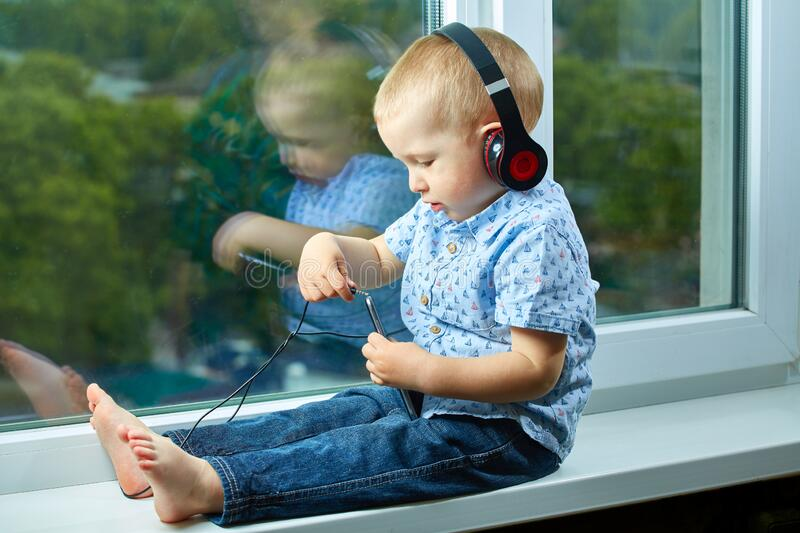 The kid sits at the window with headphones and with a mobile phone. Kid sits at the window with headphones and with a mobile phone royalty free stock photography