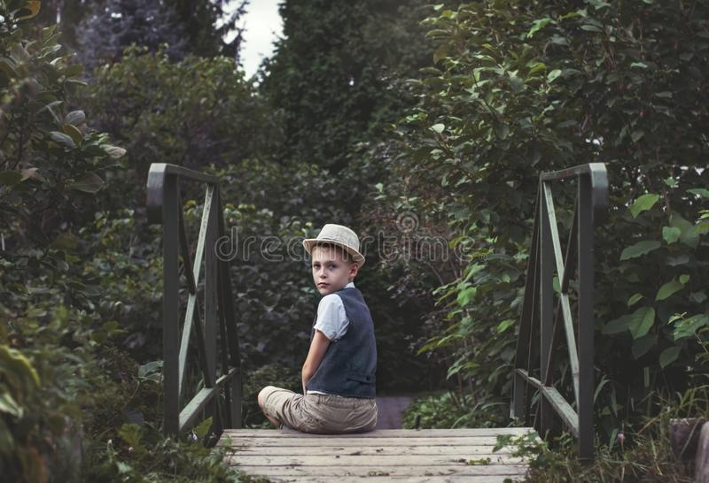 Kid sitting alone on a stairs in th garden royalty free stock photography