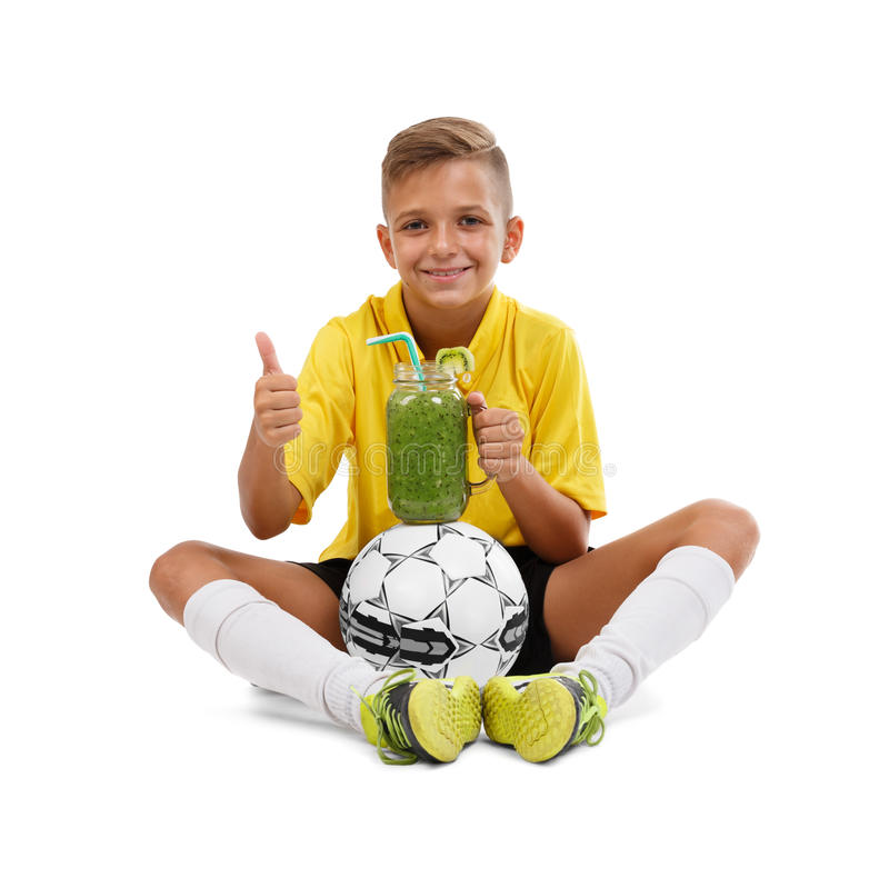Kid sitting with ball and smoothie isolated on a white background. Active schoolboy showing a thumb up. Health concept. stock images