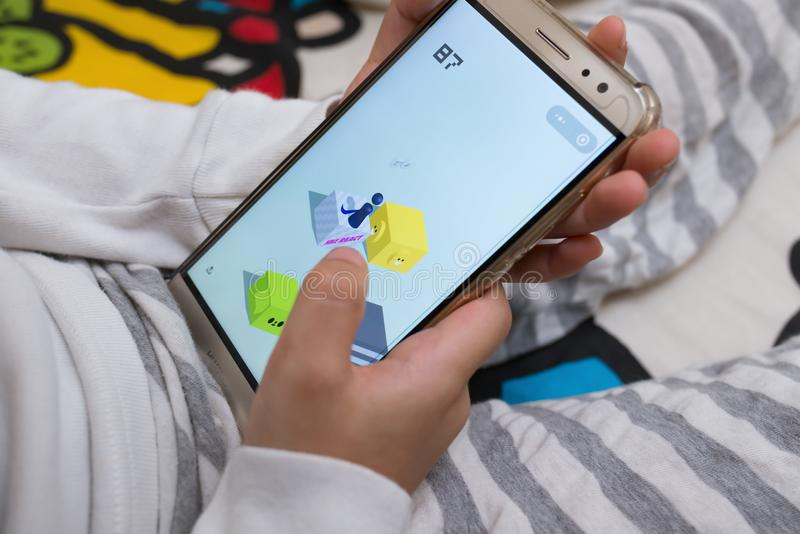 Kid sitting on bed & playing a game named little jump inside Wechat own by Tencent stock photos