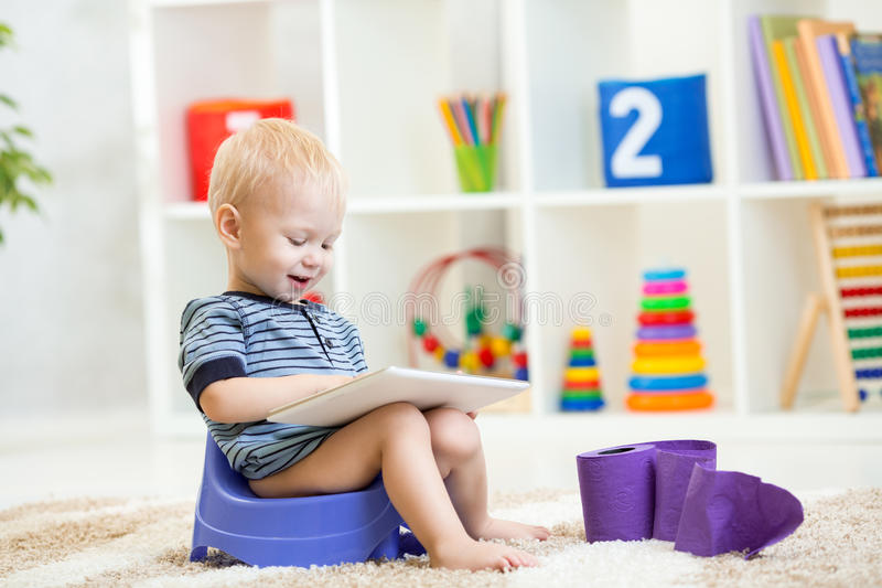 Kid sitting on chamber pot playing tablet pc stock photo