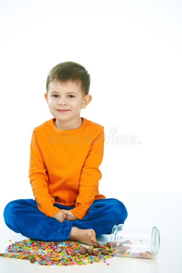Kid sitting cross-legged with sweet jar spilled stock images