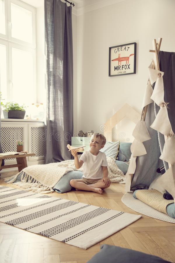 Kid sitting on the floor with toy airplane in natural playroom with comfortable bed and scandinavian tent, real photo. Kid sitting on the floor with toy airplane stock photography