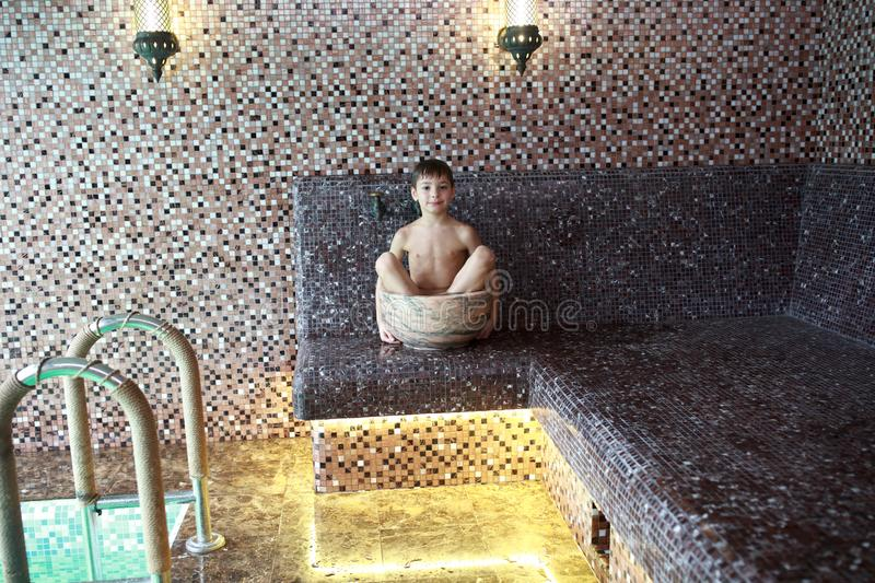 Kid sitting in hammam royalty free stock images