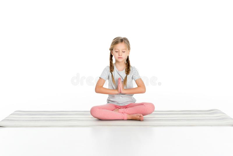 Kid sitting in lotus position on yoga mat. Isolated on white stock photo