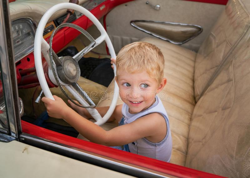 Kid sitting on old American car 50s / 60s. Beautiful child sitting on old American car 50s / 60s years, holds steering wheel and pretends to drive it.Caucasian royalty free stock images