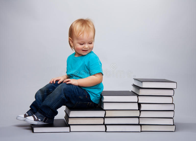 Kid sitting on a a steps made of books stock image