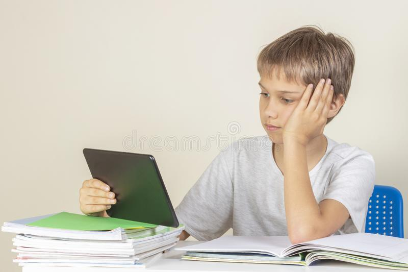 Kid sitting at table with books notebooks and using tablet computer.  stock image