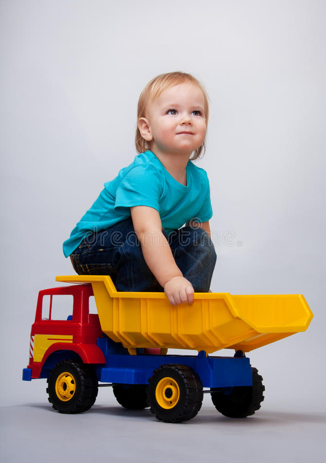 Kid sitting on a toy truck royalty free stock photo