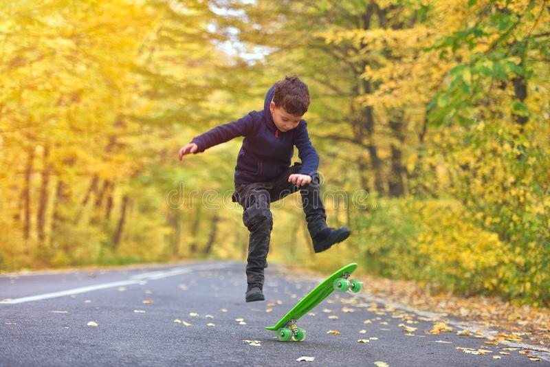 Kid skateboarder doing skateboard tricks in autumn environment.  royalty free stock photography