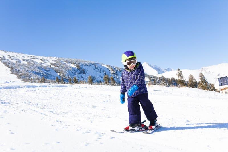 Kid in ski mask skiing on snow downhill royalty free stock photos