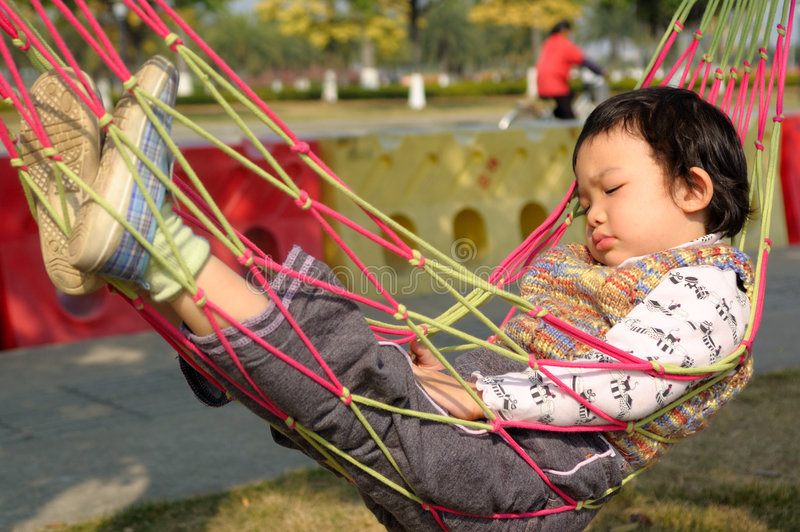 Kid sleeping. An Asian little kid sleeping on the hammock stock image