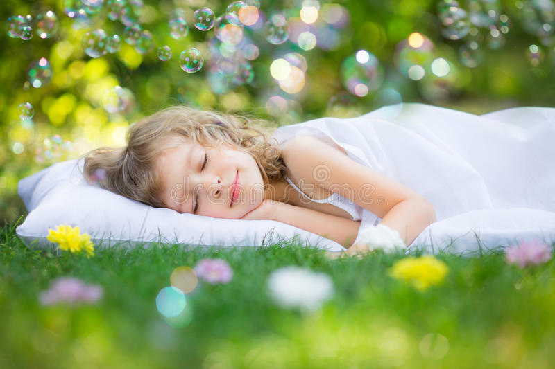 Kid sleeping in spring garden royalty free stock photo