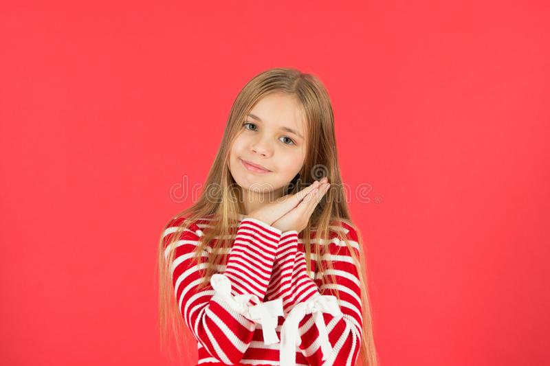 Kid small girl hold hands at cheek gesture of sleep. Good night have nice sleep. Cute peaceful girl on red background. Wish sweet dreams. Lullaby song before stock photography