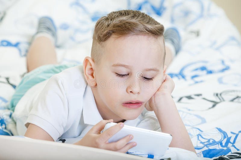 Kid with smartphone. Adorable kid playing with smartphone on the bed stock photos