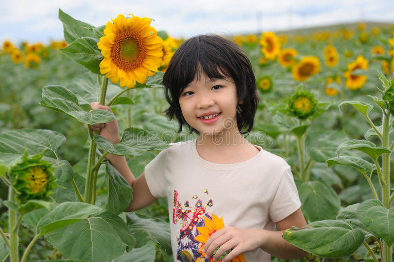 Kid smiling. A Chinese little kid smiling in the sunflower field royalty free stock photos