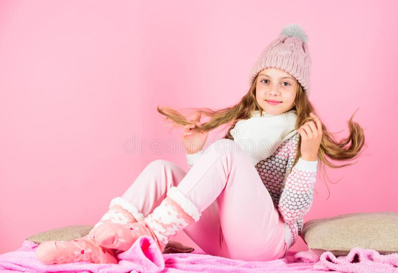 Kid smiling fashion model. Kid girl wear cute knitted fashionable hat and comfortable cozy clothes. Winter fashion royalty free stock photography