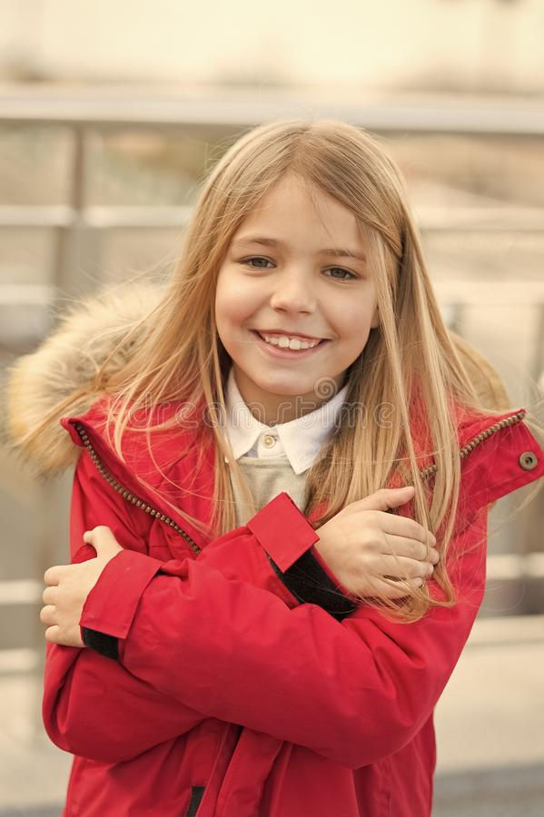Kid smiling girl wear coat jacket with fur on hood but feels cold. Cold weather concept. She is freezing. Baby hug. Herself because of cold weather. Kid try to stock images